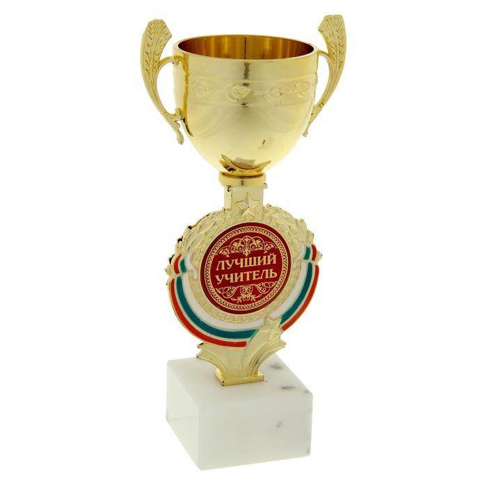 Кубок Лучший учительШкатулки, копилки, статуэтки<br>Награда выполнена в виде кубка, он дополнен цветной бляшкой, изготовленной из металла, с наименованием номинации, за которую вручается.Материал: камень, пластик.<br><br>Год: 2016<br>Высота: 188<br>Ширина: 90<br>Толщина: 60
